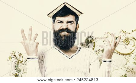 Mad Teacher Concept. Macho Sits With Open Book On Head, Like Roof. Man On Mad Face With Beard And Mu
