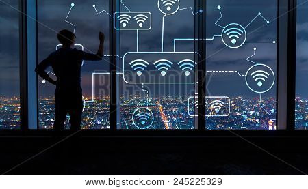 Wifi With Man Writing On Large Windows High Above A Sprawling City At Night
