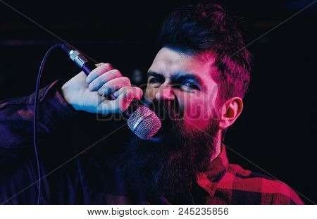 Musician, Singer Singing In Music Hall. Man With Agressive Face Holds Microphone, Singing Song, Blac