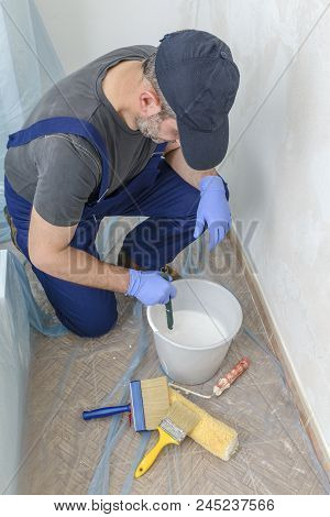 Painter Paints The Wall With The Tint Of White.