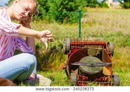 Gardening. Female Person Gardener Mowing Green Lawn With Lawnmower, Having Problem With Broken Mower