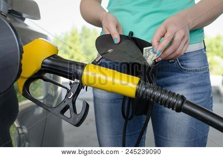 Lack Of Money For Gasoline And Fuel. Expensive Gasoline. Women Driver Showing A One Dollar And Empty