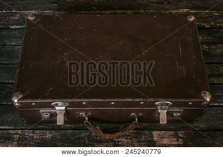 Retro Closed Suitcase On The Aged Wooden Floor Backround. Time To Pack A Suitcase And Relax.