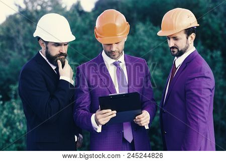 Building And Engineering Concept. Leaders With Beard And Interested Faces Discuss Project. Construct