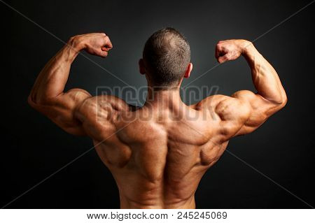 Young Bodybuilder Man Flexing Back Double Bicpes Pose, Showing His Huge Trapezius, Rhomboid, Levator