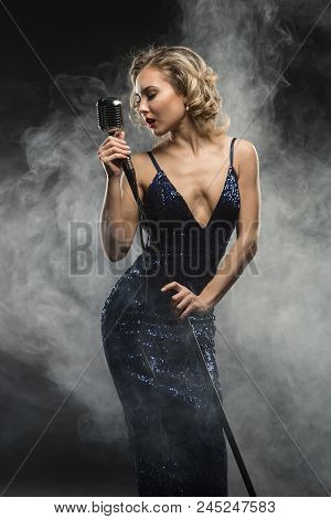 Sexy Young Girl Singer Singing With Silver Retro Microphone On Black Background With Stage Smoke