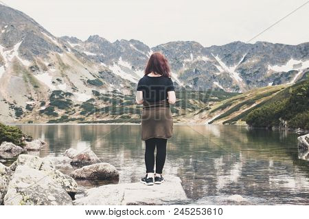 A Young Brunette Girl Stands Back And Looks At Mountain Lake And The Mountains