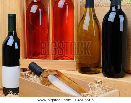 Closeup of an assortment of wine bottles on wooden crates. Horizontal format.