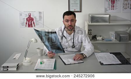 Medical Doctor Looking Patients Chest X-ray And Quietly Explain