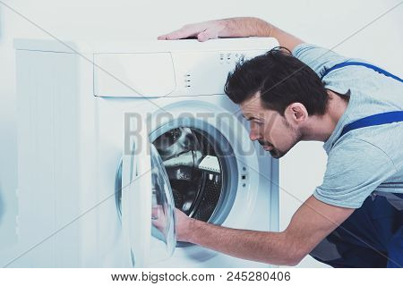 Side View Of Repairman Checking Washing Machine. Repair Of Washing Machine. White Background.