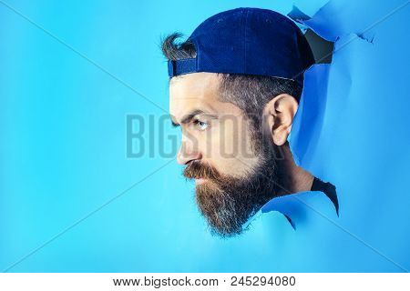 Serious Man In Cap Looking Through Hole In Blue Paper. Bearded Man Making Hole In Paper. Man Gazing