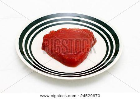 Piece of fresh tuna steak on round plate poster