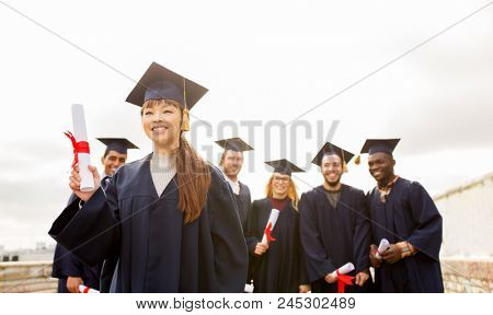 education, graduation and people concept - group of happy international students in mortar boards and bachelor gowns with diplomas