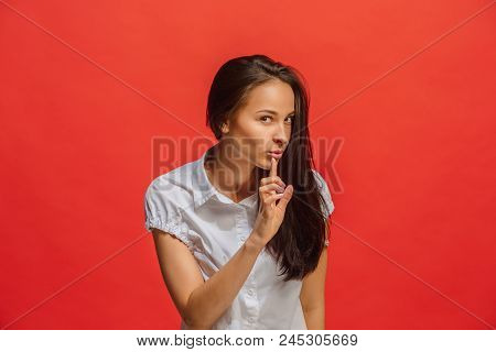 The Young Woman Whispering A Secret Behind Her Hand Over Red Background