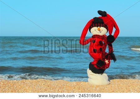 Christmas, Travel, Holidays Concept.snowman In Red Clothes Standing On The Beach.happy Snowman At Oc