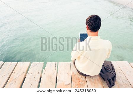 Businessman By The Sea, Working On His Digital Tablet