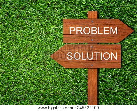 Business Solution, Solving Problem, Strategy And Planning Concept, Wooden Sign On Green Grass Backgr