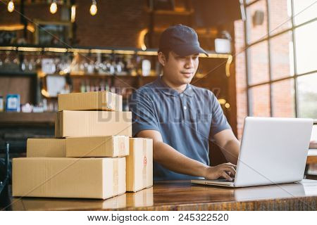 Online Shopping Young Start Small Business In A Cardboard Box At Work. The Seller Prepares The Deliv