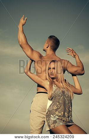 Tenderness And Strength Concept. Woman And Man Holding Hands On Blue Sky. Girl With Blond Hair And M