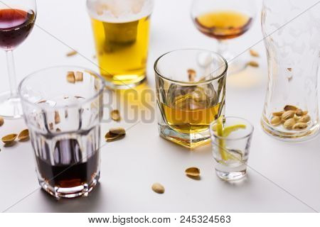 alcohol addiction and drunkenness concept - glasses of different drinks on messy table poster