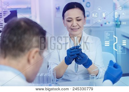 Herb In A Test Tube. Careful Attentive Biologist Holding A Test Tube And Smiling While Looking At Th