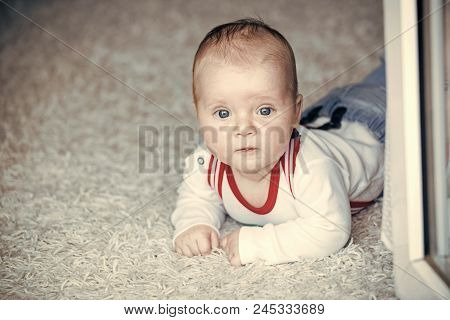 Innocence, beauty, purity. Baby with blue eyes on adorable face. Infant crawl on floor carpet. Child development concept. Childhood, infancy, newborn. poster