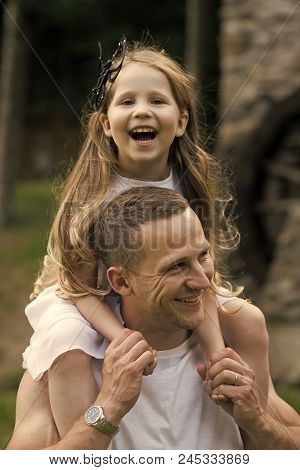 Girl On The Shoulders Of Dad. Girl Child Smile On Man Shoulders On Summer Day Outdoors. Happy Family