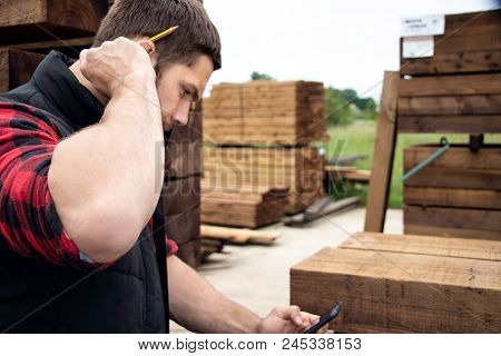 Storesman at small business lumber yard counts stock and records it with his mobile device, phone. poster