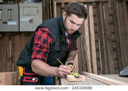 Handsome Carpenter, Wood Worker Man Measures And Drills Timber In Wood Workshop Of Small Business