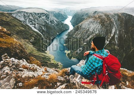 Man With Backpack Relaxing On Mountain Summit Traveling Alone In Norway Lifestyle Adventure Vacation