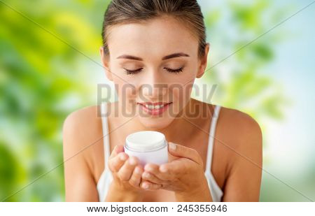 beauty, cosmetics, skin care and people concept - close up of beautiful happy woman holding and smelling cream jar over green natural background