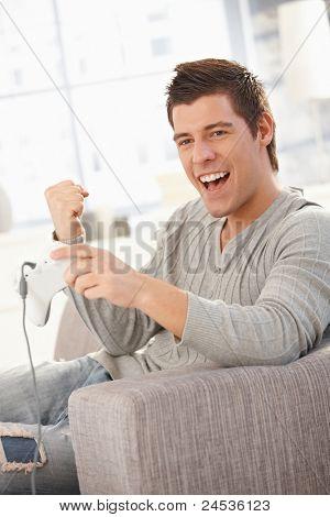 Young man enjoying playing computer game, holding joystick, raising fist, laughing.?