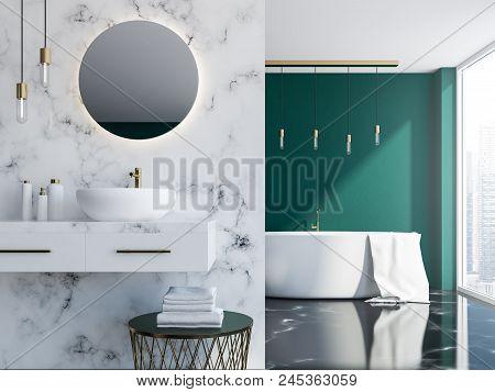 White Marble And Dark Green Loft Bathroom With A Sink, A Round Mirror And A Tub Near A Loft Window.