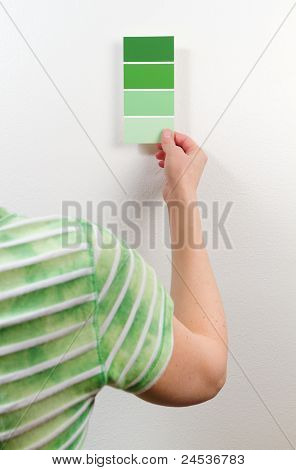 Woman Choosing Among Green Paint Swatches