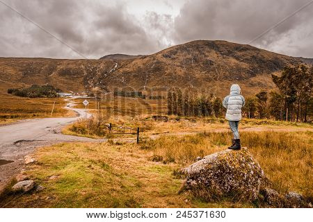 A Female Hiker Standing On A Rock Amidst The Yellow Grass, Looking Towards The Mountains In The Dist