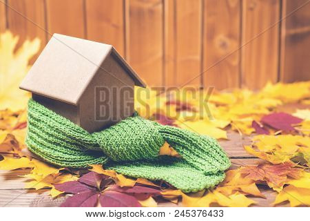 Green Scarf Around A Miniature House On The Autumn Leaves Background. Concept Of Protecting Or Isola