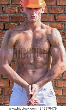 Athlete Posing With Sexy Nude Torso In Hard Hat. Builder With Strong Muscular Body Covered With Dust