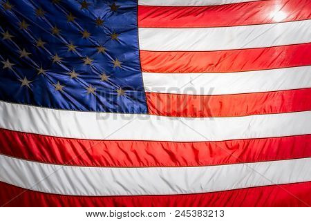 The Sun Shining Behind The Stripes Of An American Flag.