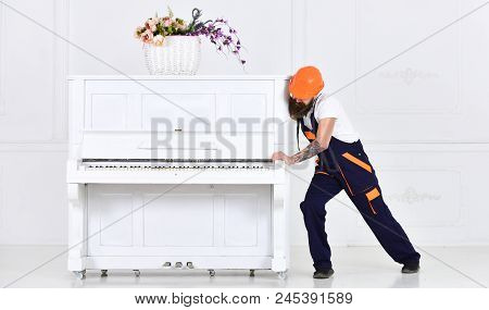 Man with beard worker in helmet and overalls pushes, efforts to move piano, white background. Loader moves piano instrument. Courier delivers furniture, move out, relocation. Heavy loads concept. poster