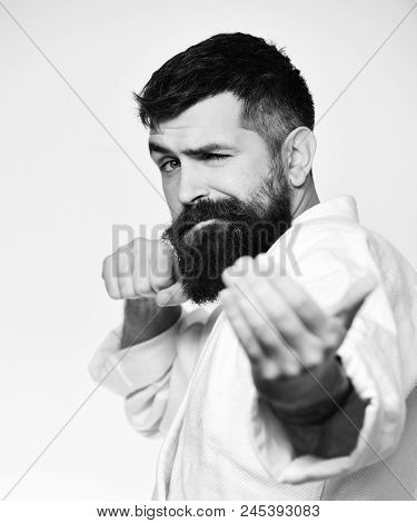 Karate Man With Flirty Face In Uniform. Taekwondo Master Practices Attack And Provokes Fight. Man Wi