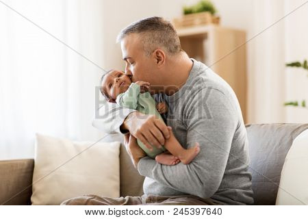 family, fatherhood and people concept - happy father with little baby boy sitting on sofa at home