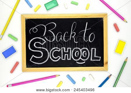 Back To School White Chalk Lettering On Blackboard With Colorful Art Supplies. Back To School Banner