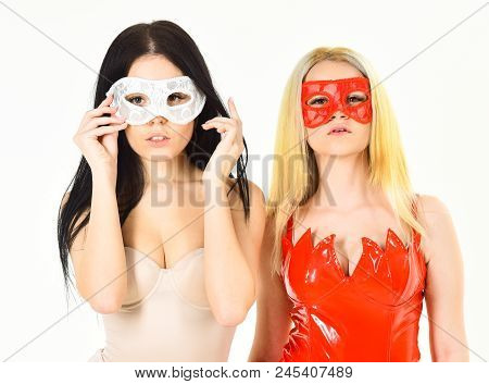 Sinfulness and purity concept. Girls dressed as devil and angel, isolated white background. Angel and demon in masks, women play role game anonymously. Sexy girls in bodysuits looks attractive. poster