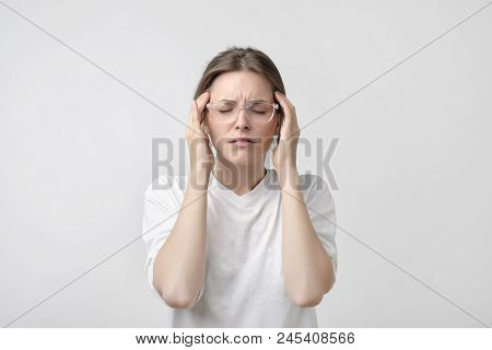 European Girl In White T-shirt Suffers From Terrible Headaches And Compresses The Head With Fingers.