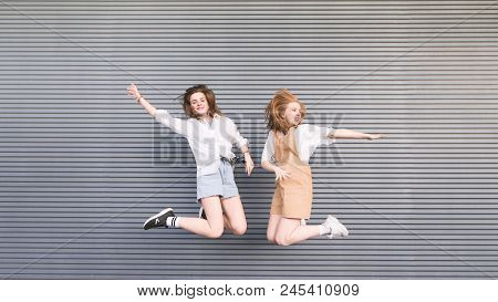 Two Stylish Happy Girls Jump Together On A Gray Background. Portrait Of Smiling Fashionable Girlfrie