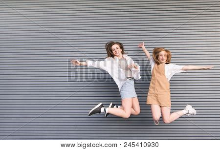 Two Happy Girls In Bright Summer Clothes Jump On The Background Of A Gray Wall, Look Into The Camera