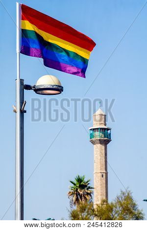 The minaret of Hassan Bek Mosque and a pride rainbow flag, in the day of the Pride Parade, in Tel-Aviv, Israel poster