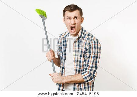 Young combative angry housekeeper man in checkered shirt holding and sweeping with green broom isolated on white background. Male doing house chores. Copy space for advertisement. Cleanliness concept poster