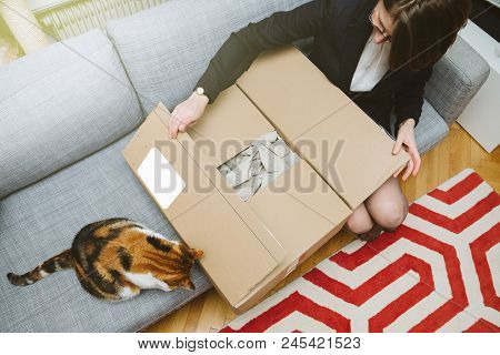 Business Woman Unpacking Unboxing Cardboard Box  Being Helped By Her Pet Cat Beautiful Animal
