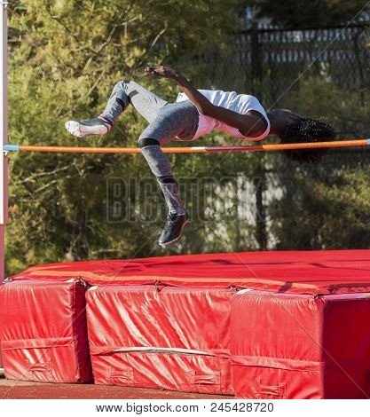 Female High School Track And Field Athlete Is Over The Bar While Competing In The High Jump.